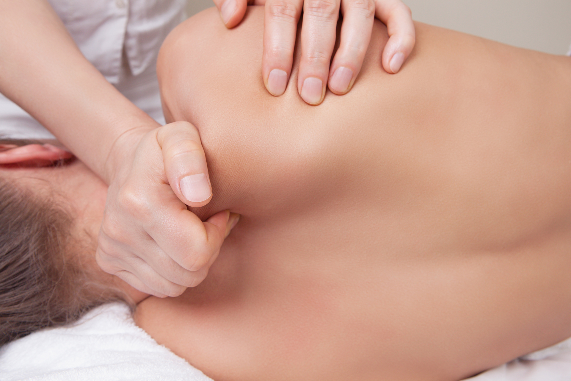 Professional  therapist doing neck and shoulder deep tissue and